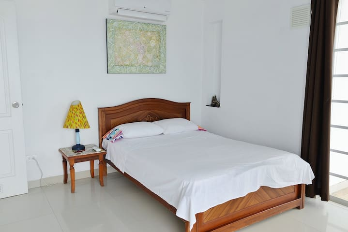 The main room is spacious, offers a full-size bed, closet space, and has direct access to the balcony.