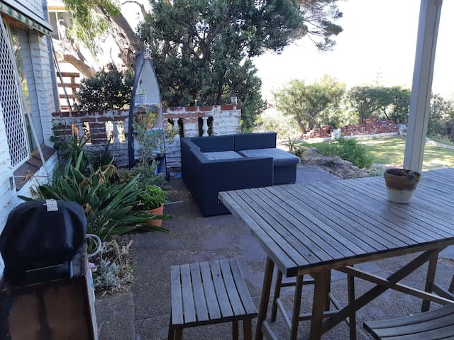 Outside living area. Tall table with stools and outdoor couch to relax and unwind.