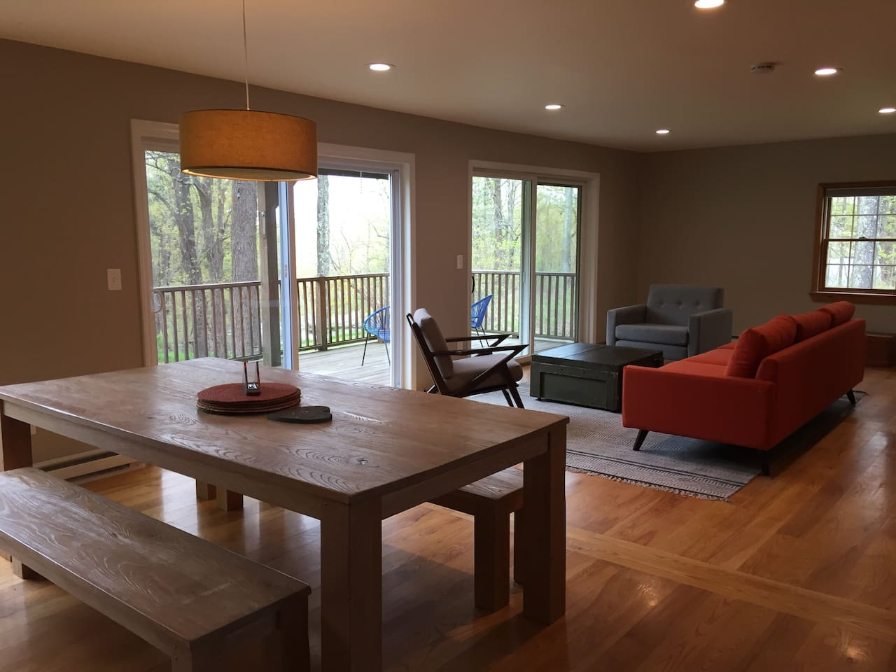 Dining table with seating for 10, living area with view out to landscaped yard