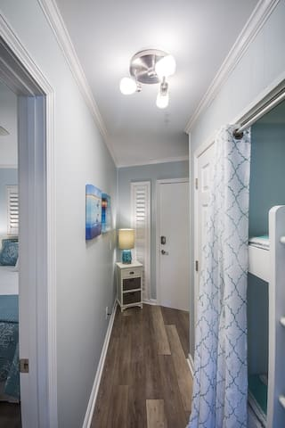 Hallway and Bunks to Right.  Six beach towels in bins by front door.  Sun screen, after sun aloe vera, beach umbrella and beach toys in closet.