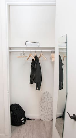 Your very spacious closet, hangers + ironing board + mirror