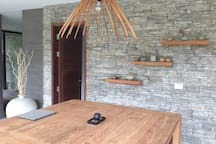 dining area with solid teak wood dining table with 4 chairs, and teak wood floating shelves into the stone wall