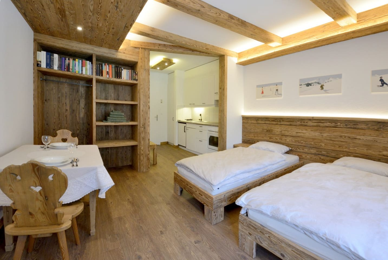 Wohn- und Schlafbereich mit Küche und Eingang im Hintergrund