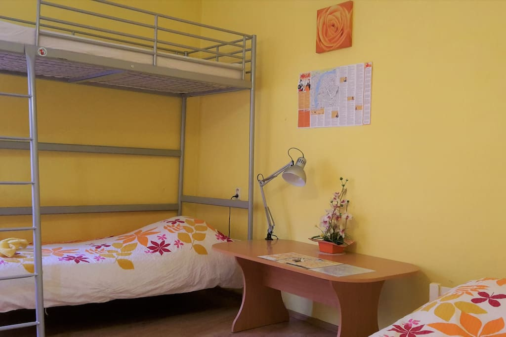 The furniture includes: Two single beds, a loft bed, night tables, large wardrobe, desk with chairs.