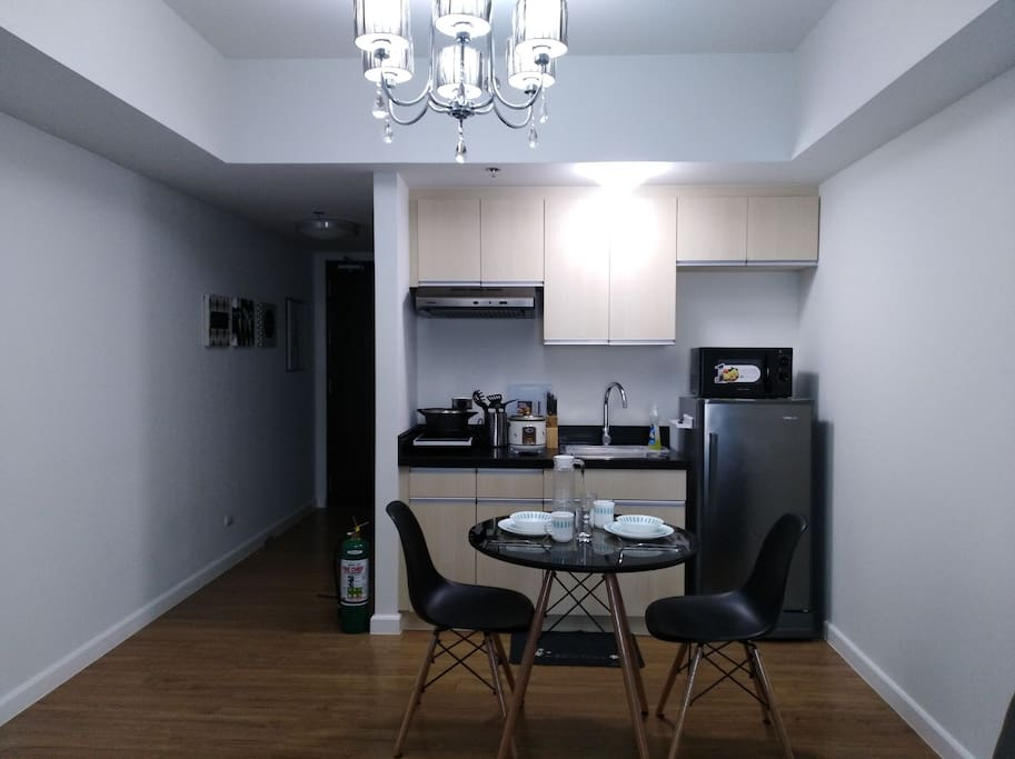 Dinning and kitchen wares are placed in the kitchen cabinets. Only the microwave, water heater, and induction cooker are seen when entering the unit.
