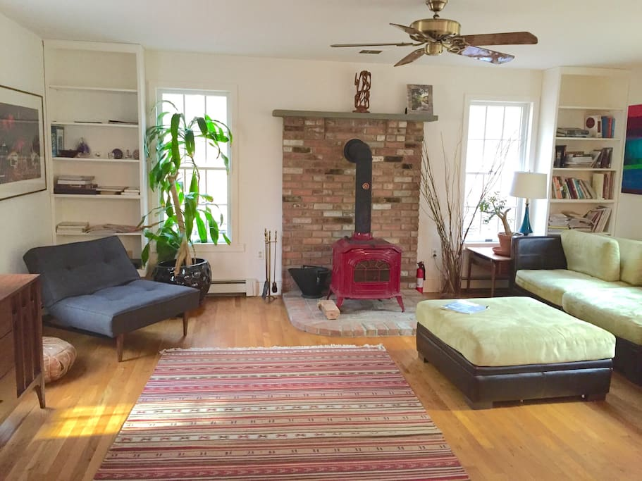 Ultra comfortable living room soaked in natural light and with a cozy wood burning stove.