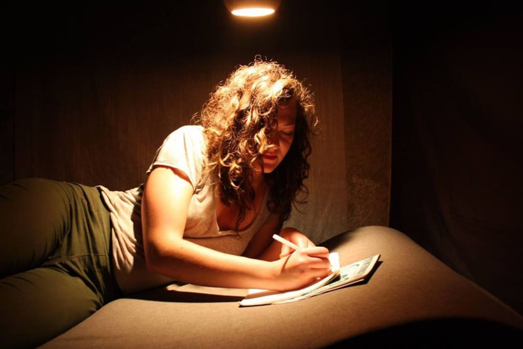 Una writes under d una light inside poets corner room is a prison cell darkness surround her hot light certainly pen to paper went well