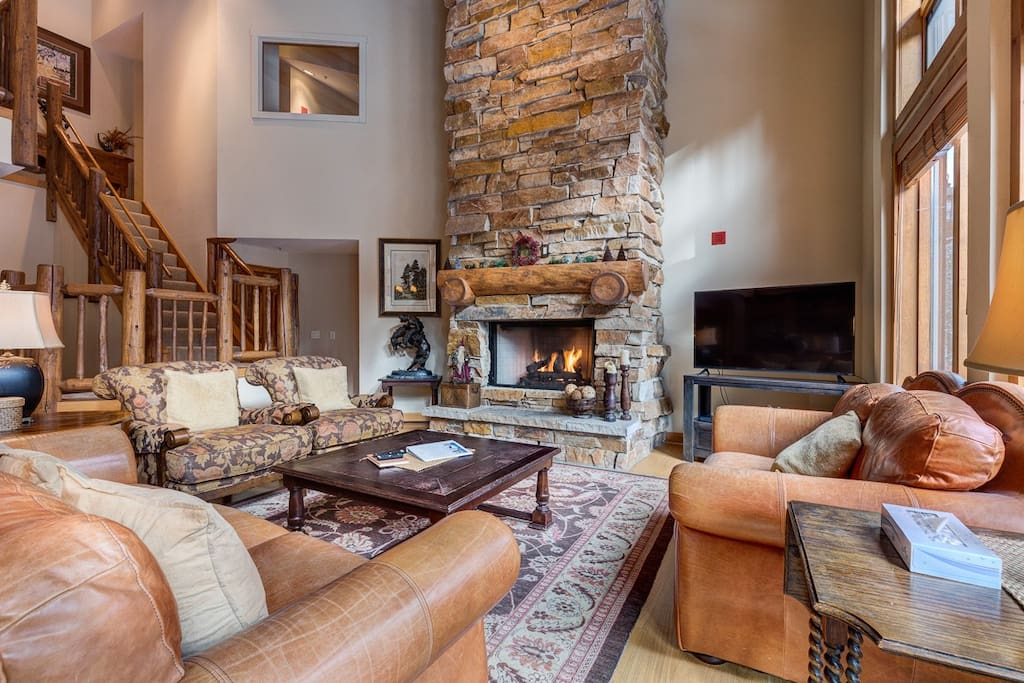 The living area features vaulted ceilings, a beautiful gas fireplace with stone extending to the ceiling and a wall of windows featuring scenic views.