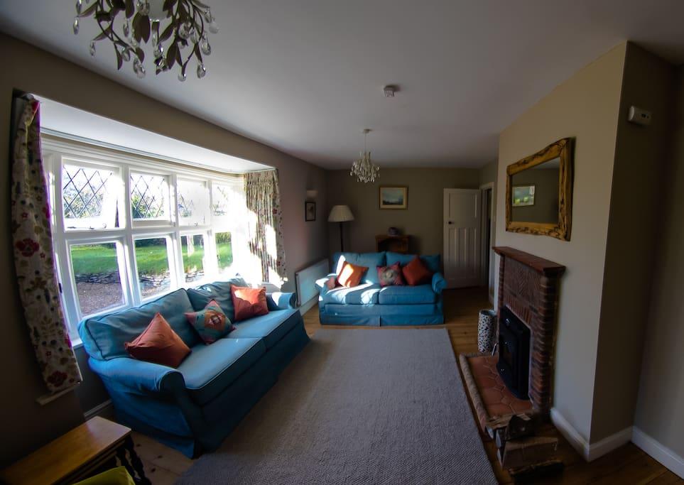 Large sitting room with wood-burning fireplace