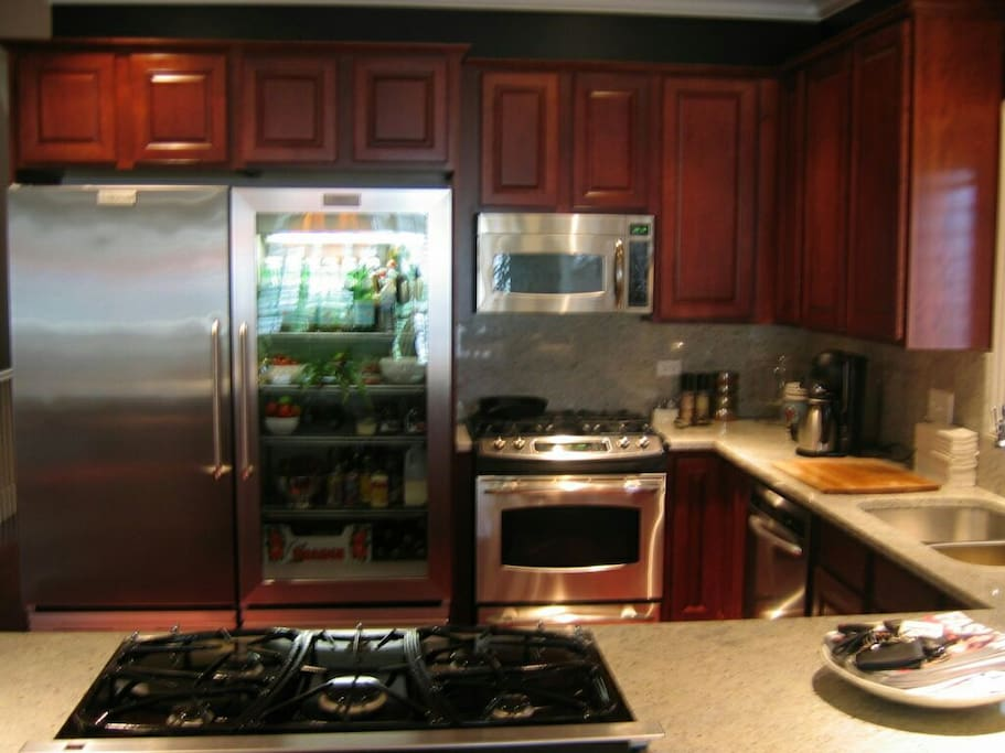 Full chef quality kitchen with two cooktops,  microwave, coffee maker,  espresso machine, and significant cookware,  flatware,  and glassware.
