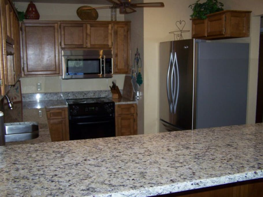Updated and fully stocked kitchen with granite countertops and stainless steel appliances