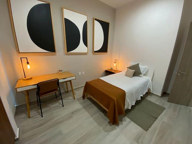 Habitación cama individual y escritorio de trabajo