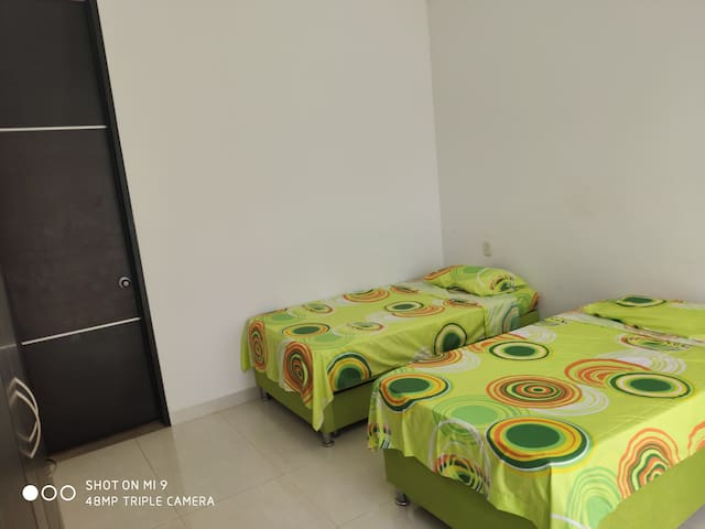 Habitación 3, con baño privado y closet.   Dos camas sencillas cada una con nido.  Ventilador de pedestal.
