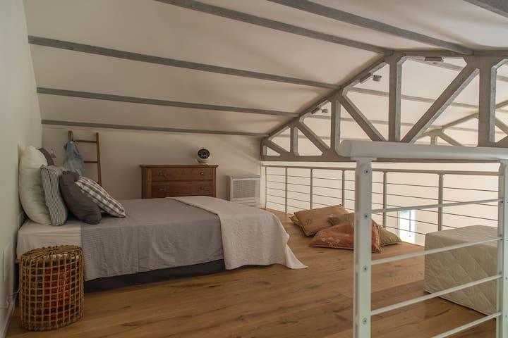 La stanza da letto sul soppalco. The bedroom, on the mezzanine.