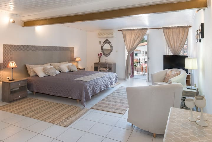 Κρεβατοκάμαρα (γενική άποψη) με μπαλκονάκι, καθιστικό με πολυθρόνες και μεγάλης οθόνης τηλεόραση