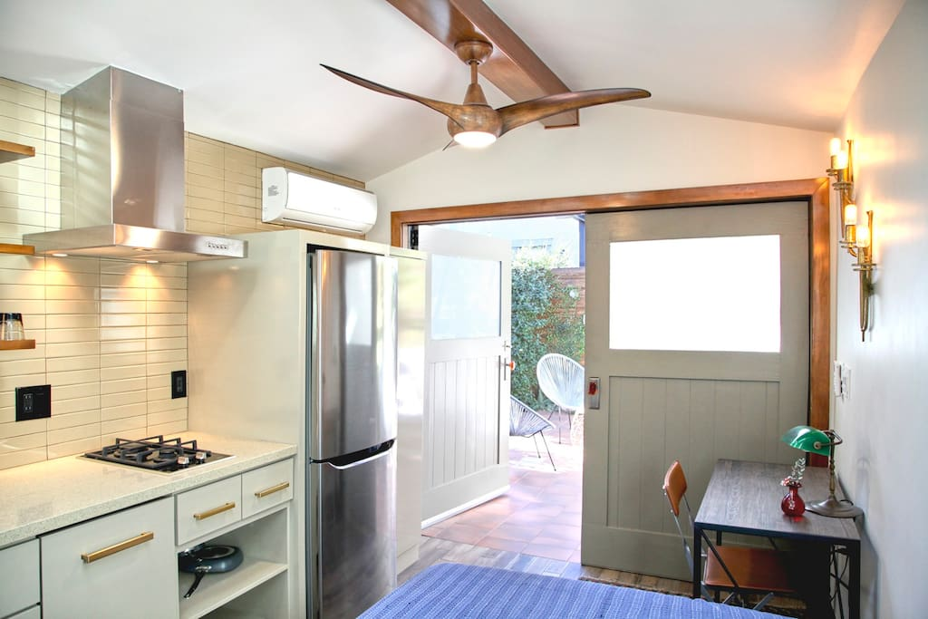 Full sized desk and Refrigerator, both doors open onto the patio creating a seemless indoor outdoor enviroment.