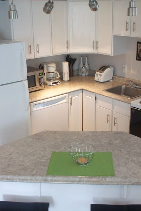 Full kitchen with island seating and dining table. Dishes are provided for use, and dishwasher for convenience.