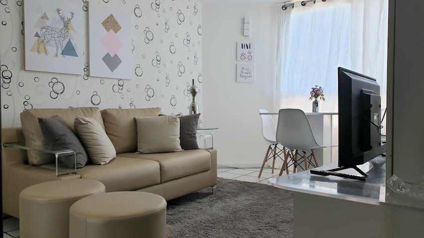 Sala de estar com ventilador de teto e TV tela plana Full HD.