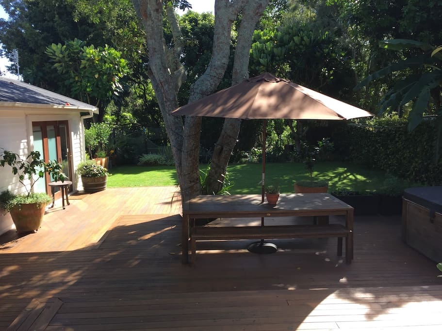 Private tree-lined sunny deck & lawn with BBQ, outdoor dining, trampoline and Spa Pool