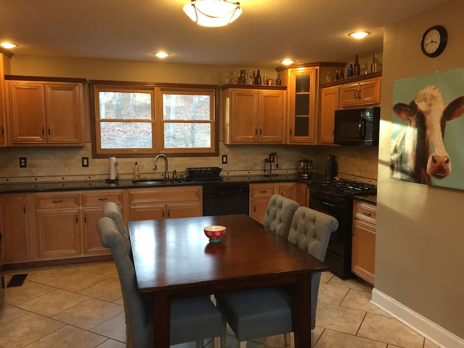 Large kitchen/ dining area with custom granite counter-tops, cherry cabinets, and gas stove/oven.