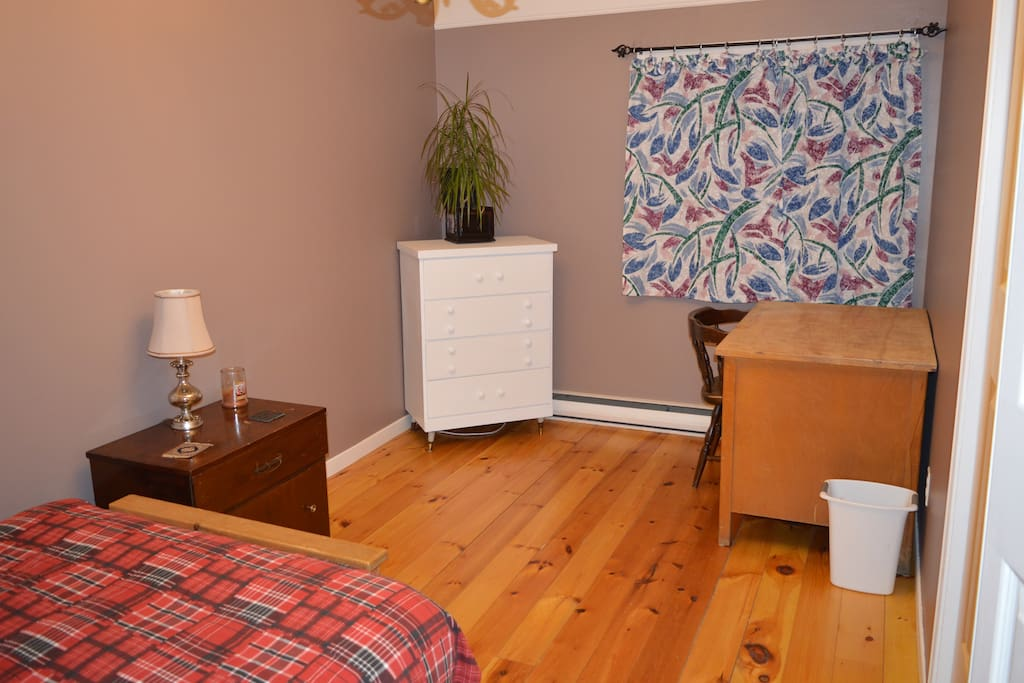 Spacious master bedroom with beautiful knotty-pine floor