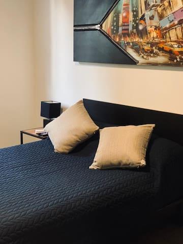 Confortable habitación con TV de paga, cama matrimonial. Cuenta con utensilios para planchar ropa.
