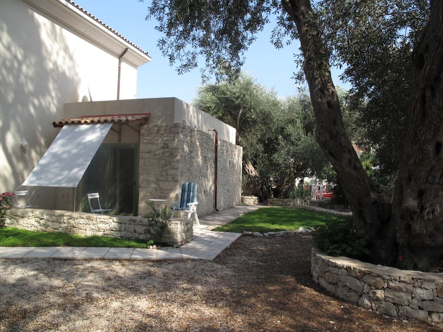 The Studio  is protected by a 50cm stone walls, lush green garden and olive trees