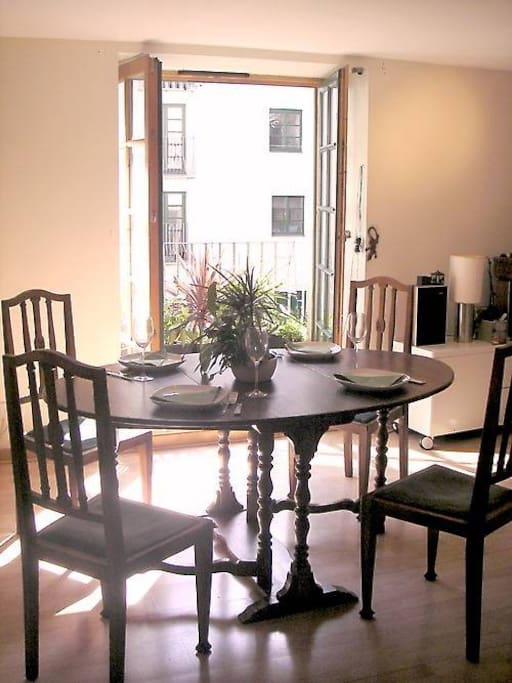 Dining area in front of French windows and Juliet balcony overlooking landscaped courtyard.