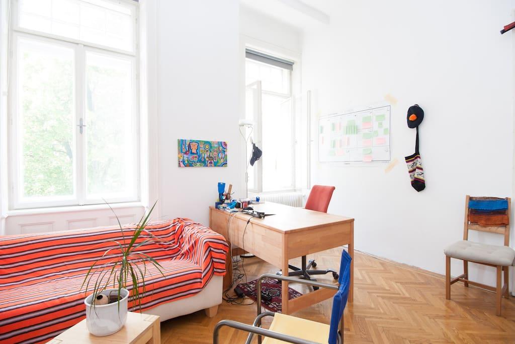 Room including desk and couch / Zimmer mit Couch und Tisch