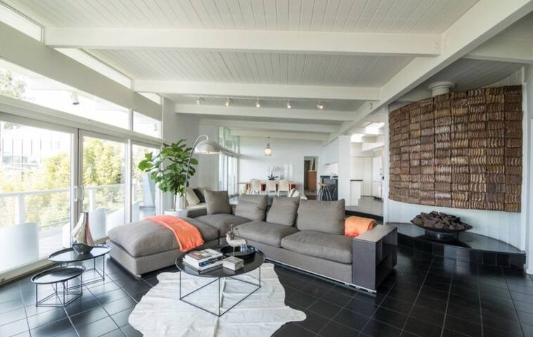 High ceilings and floor to ceiling windows and sliding doors bring the outside in ....