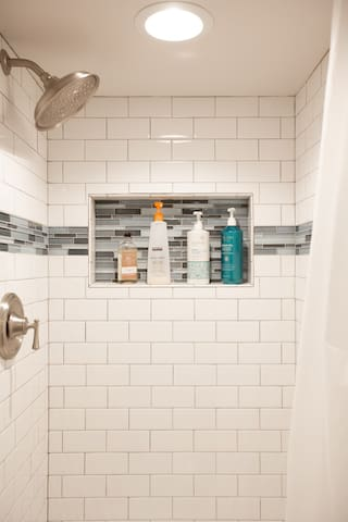 Updated newly built shower stocked with shampoo, conditioner and body wash.