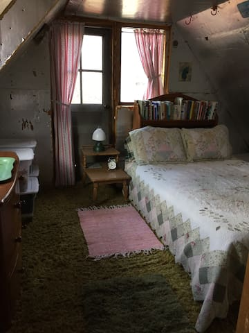 A queen size bed and more books are in the upstairs bedroom.