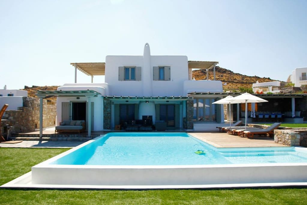 Huge outdoors with grass and private heatable pool and dining areas