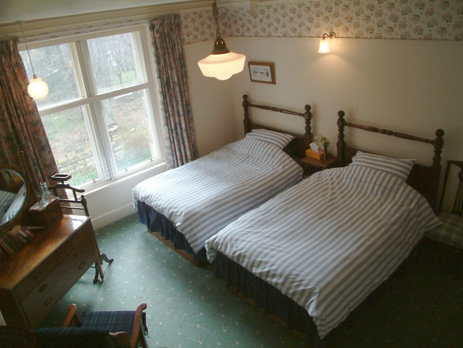 'Owl'  Twin room with four shared show/bathrooms. Views over the garden into the woods.