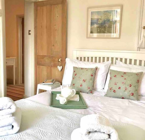 Stylish front bedroom with Laura Ashley bed linen and soft fluffy towels! Shutters on window and lined curtains.