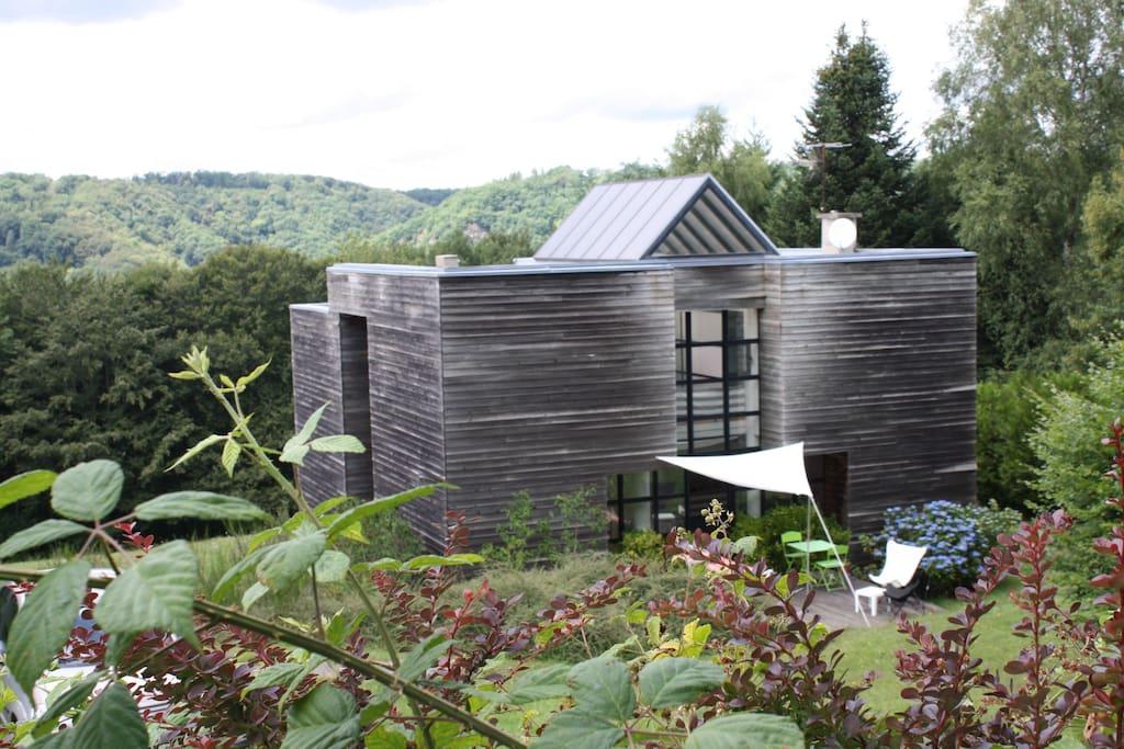 Maison sur un grand terrain, dans verdure. Grandes ouvertures en alu mais pas de volets mais des rideaux aux fenêtres des chambres.
