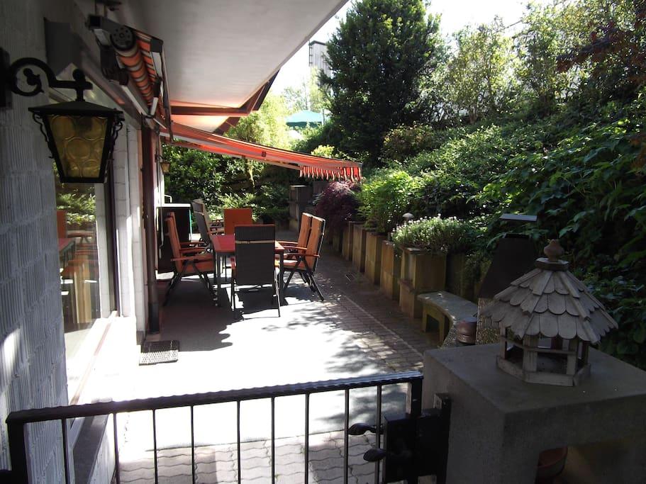 Blick auf die Terrasse mit dem kleinen Garten am Hang