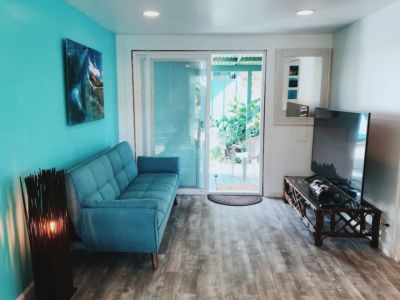 """Relax on our fold out futon and enjoy the 60"""" flat screen TV after some long days in the sun :)  Also our slider door gives you a direct path to the Garden , bathroom and kitchen area!"""