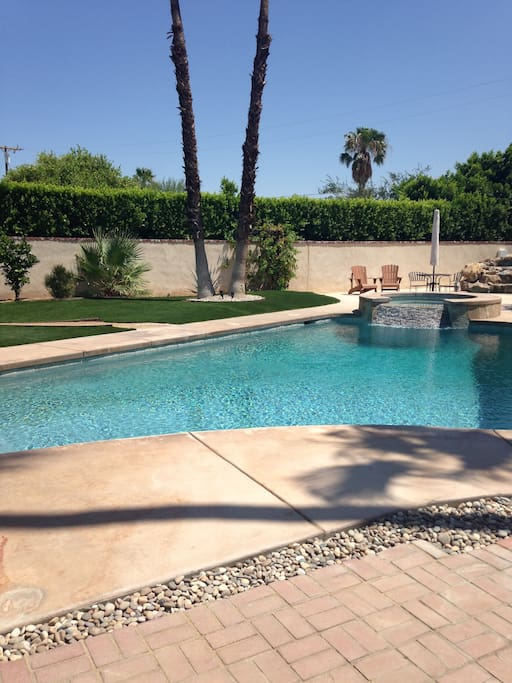 View from attached patio towards back of property. Extra large salt water pool and attached spa.