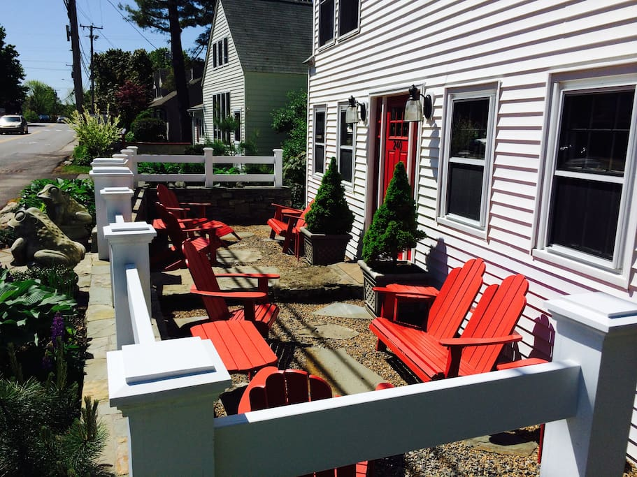 Sunny front courtyard with Adirondack chairs is perfect for people watching.