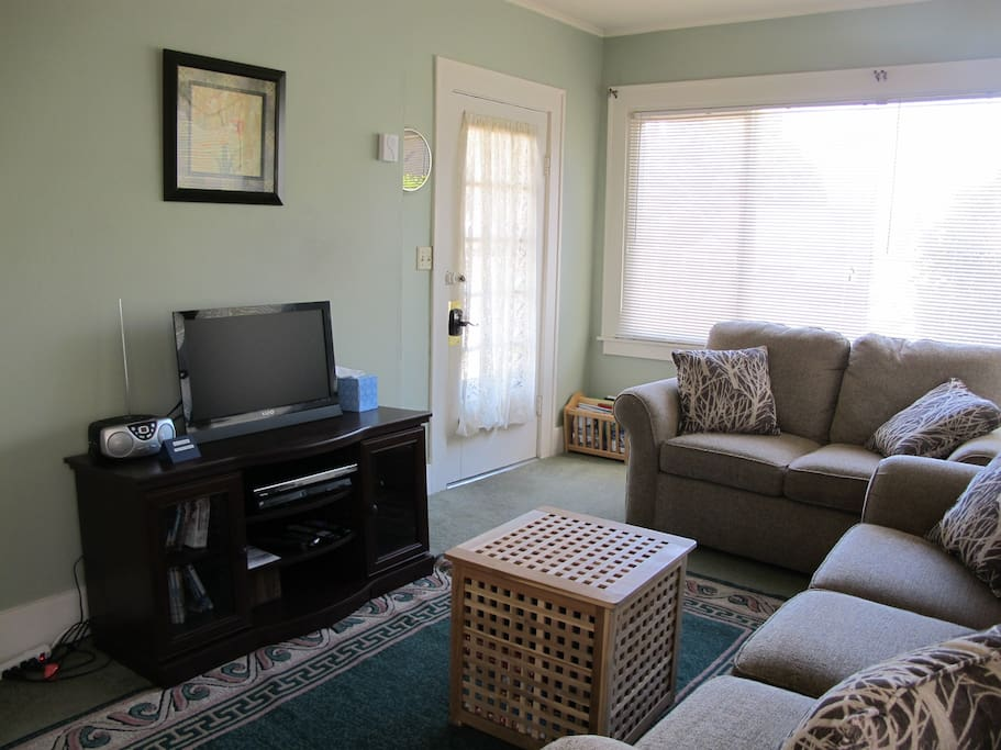 Living room area, with HDTV, DVD player, radio/cd player and a selection of dvds and cds.