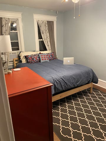 Middle bedroom with queen size bed, AC unit and ceiling fan. Bedside lamps feature USB ports and both warm and cool light settings.