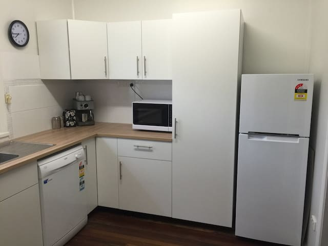 Full featured kitchen with fridge, microwave, dishwasher, and coffee making facilities.