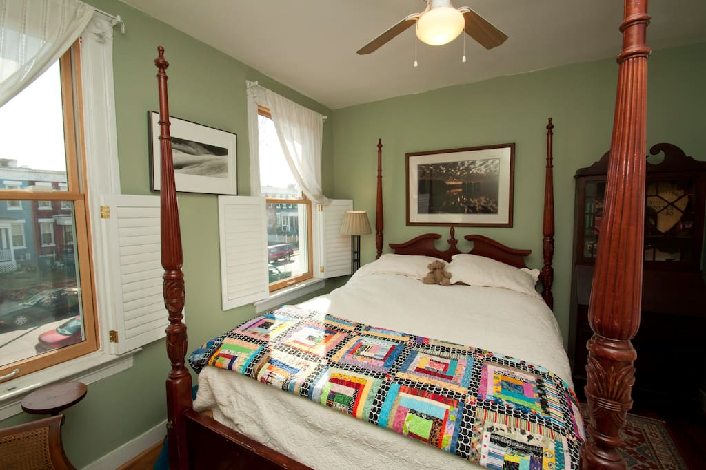 Queen sized four poster hardwood bed in one bedroom.