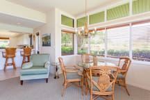 The living room features a dining table with comfortable seating for four