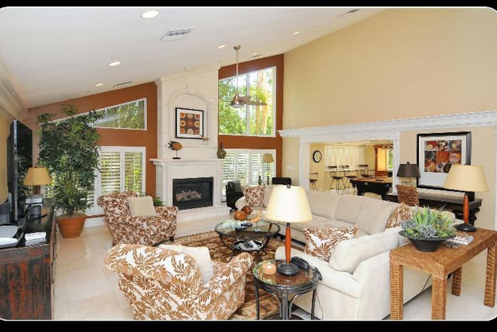 The grand room is complete with fireplace, desk, living room and formal dining room.