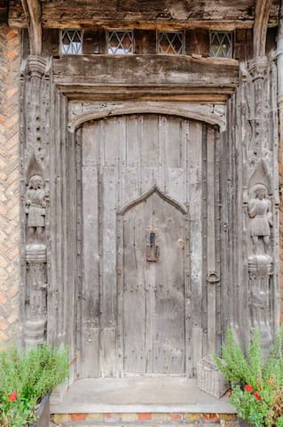 One of the most photographed doors in the world. Our medieval front door with original hand carved huntsmen figures either side.