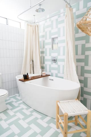 A huge tub with a rain shower head creates a spa-like experience in the guest bathroom.