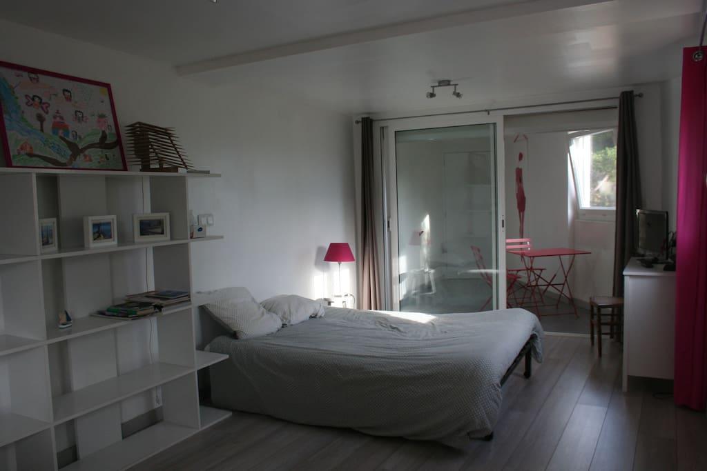 Vue d'ensemble du studio : lit ; étagère ; commode ; télé et véranda au fond