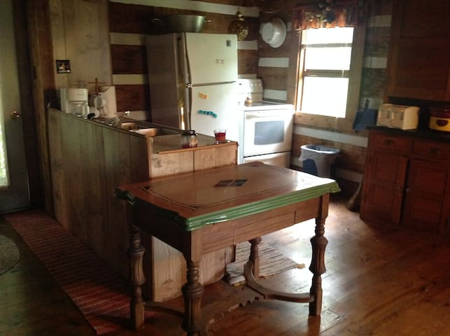 Fully equipped kitchen with microwave, coffee pot, refrigerator, stove and a full cabinet of dishes